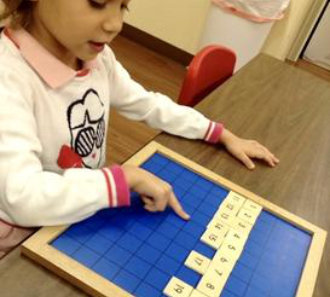 little girl playing word board